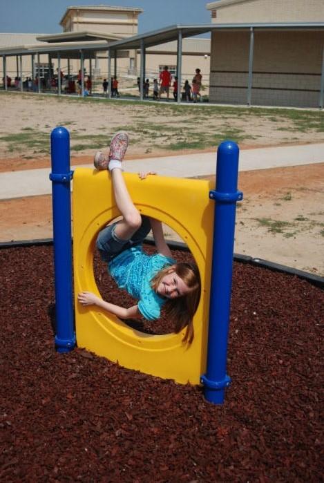 child playing on freestanding playground equipment